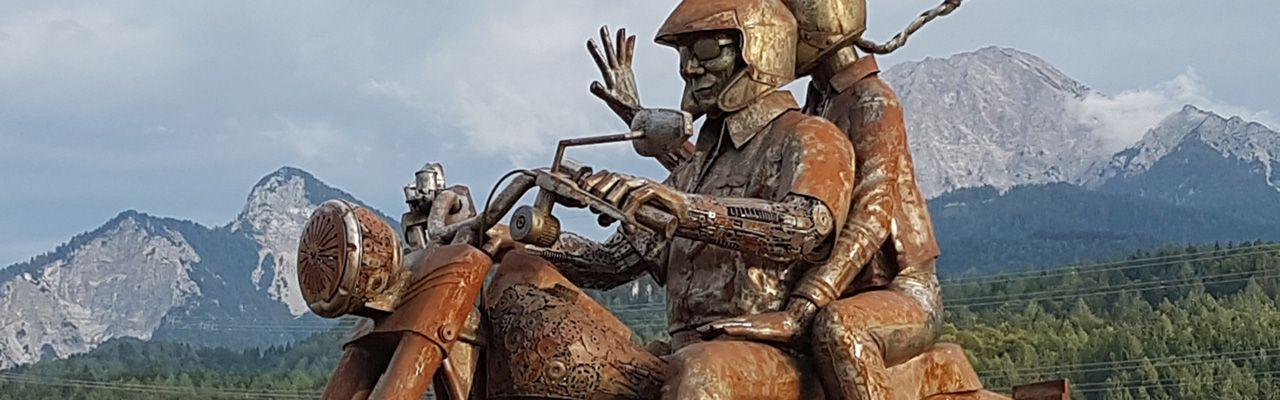 Auf dieser Skulptur einer Harley Davidson sitzen zwei Motorradfahrer auf einem rostigen Bike. Hinter ihnen sieht man Berge